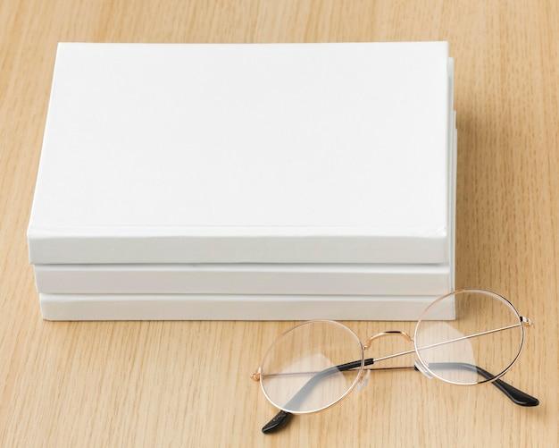 Libro piatto disteso sul tavolo con gli occhiali accanto
