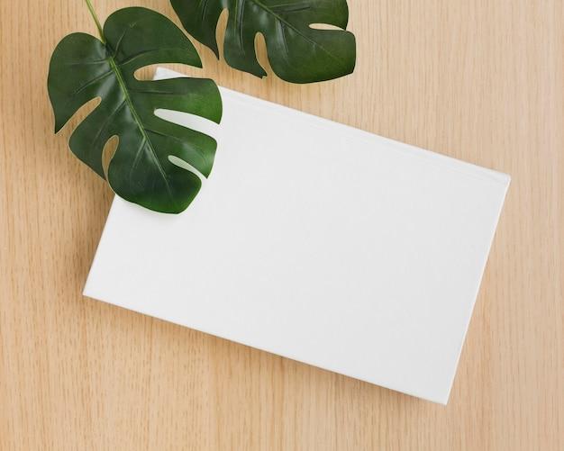 Libro piatto laico sul tavolo con foglie di piante