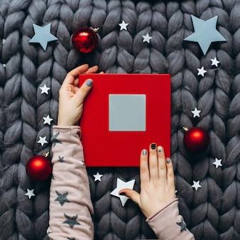 Libro rosso di natale con le palle nella coperta lavorata a maglia grigia
