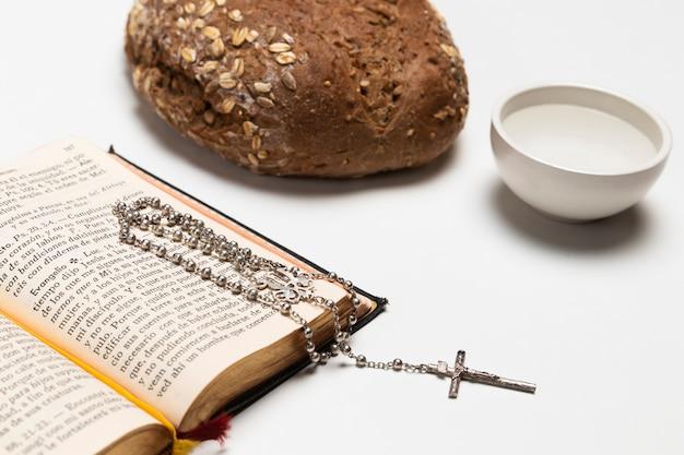 Libro sacro del primo piano con pane e acqua