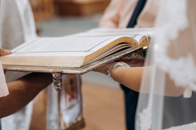 Libro sacro della bibbia sulle mani della sposa sul rituale sacramentale delle nozze in chiesa