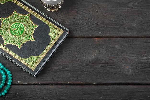 Libro sacro islamico corano con sfondo di rosari