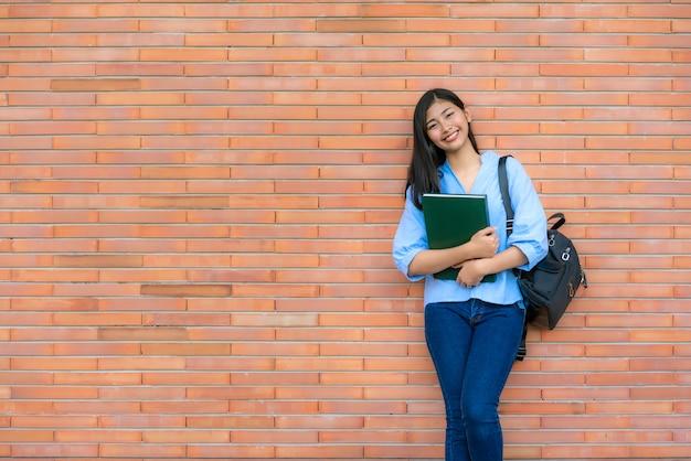Libro sorridente asiatico della tenuta della studentessa che posa sul muro di mattoni in città universitaria.