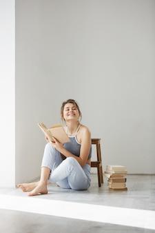Libro sorridente della tenuta della giovane bella donna tenera che si siede sul pavimento sopra la parete bianca nelle prime ore del mattino.
