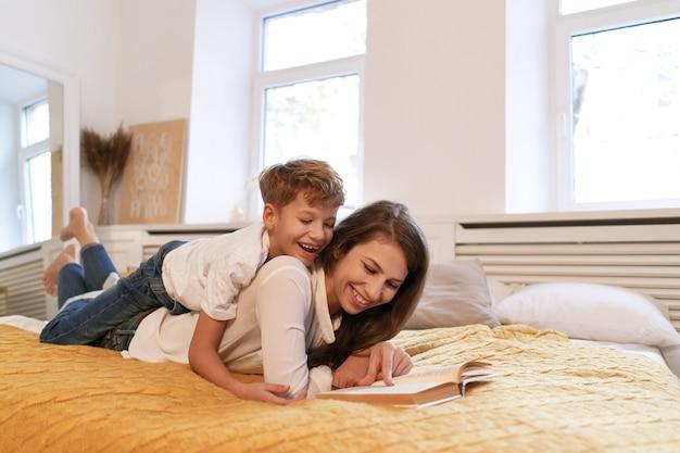 Libro sorridente di abbraccio e di lettura della madre e del figlio insieme