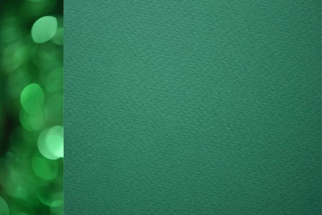 Libro verde strutturato del primo piano con la linea verde del bokeh dalla parte di sinistra