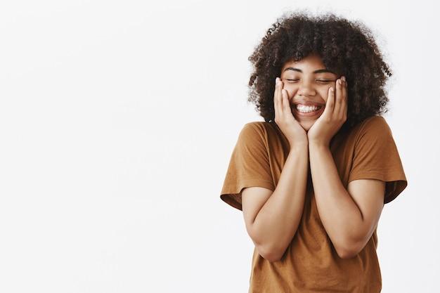 Lieta donna afroamericana innamorata che sente eccitazione e affetto sollevata e toccata dopo un grande appuntamento in un luogo romantico tenendosi per mano sul viso chiudendo gli occhi e sorridendo ampiamente