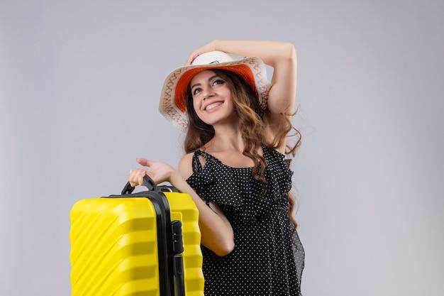 Lieta giovane bella ragazza viaggiatore in abito a pois in cappello estivo tenendo la valigia cercando sorridente allegramente felice e positivo in piedi su sfondo bianco