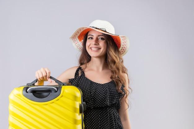 Lieta giovane bella ragazza viaggiatore in abito a pois in cappello estivo tenendo la valigia guardando la telecamera sorridendo allegramente felice e positivo in piedi su sfondo bianco