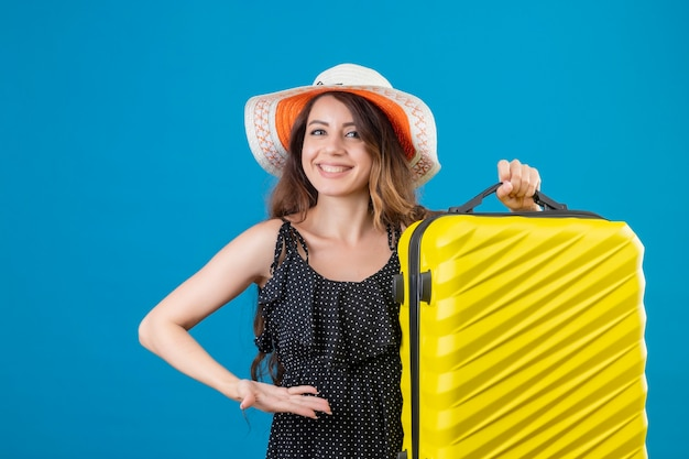 Lieta giovane bella ragazza viaggiatore in abito a pois in cappello estivo tenendo la valigia guardando la telecamera sorridendo allegramente felice e positivo in piedi su sfondo blu