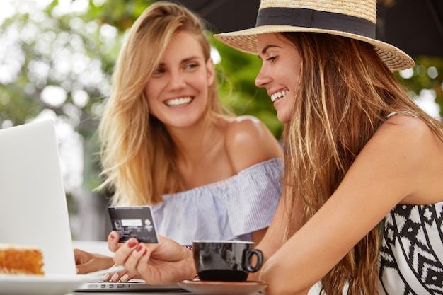 Lieta giovane donna bruna in cappello di staw felice di ricevere lo stipendio, spendere soldi per lo shopping online, trascorre il tempo libero con un amico al bar, godersi un caffè. persone, e-commerce e concetto di pagamento