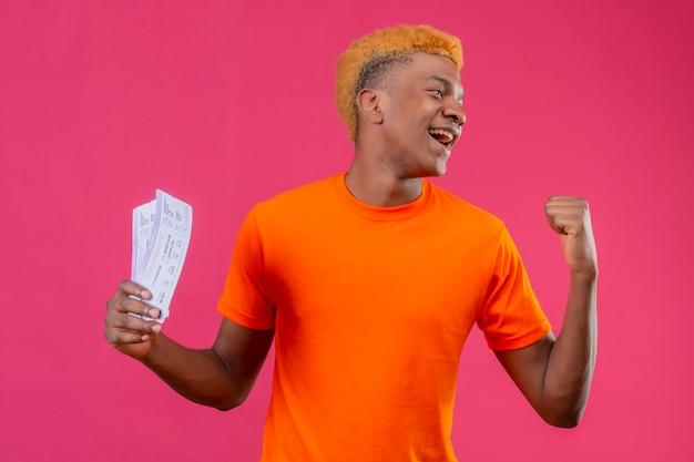 Lieto giovane ragazzo bello che indossa la maglietta arancione che tiene la valigia di viaggio sorridendo felice ed uscito alzando il pugno rallegrandosi del suo successo in piedi sopra il muro rosa