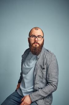 Lifestyle successo giovane con gli occhiali, barba, giacca di jeans alla moda in attesa
