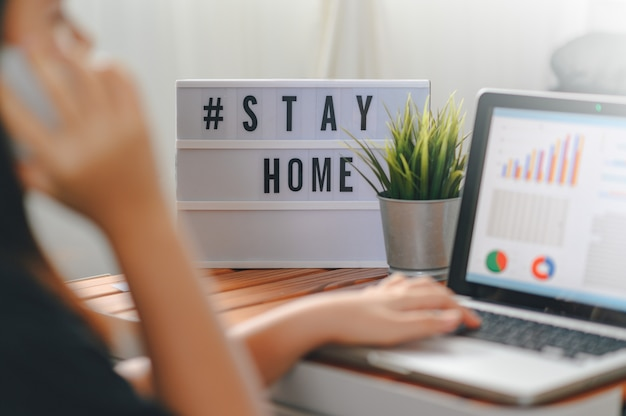 Lightbox con hashtag di testo #stayhome incandescente in luce e sfocata donna che lavora a casa. impiegato in quarantena. lavoro a domicilio per evitare malattie da virus. libero professionista o concetto di lavoratore a distanza.