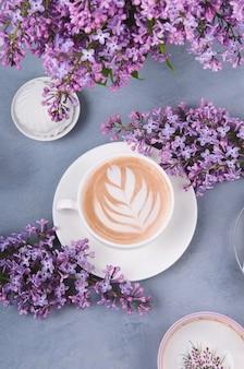 Lillà, caffè con latte art e marshmallow sul tavolo di legno grigio. mattina romantica disteso