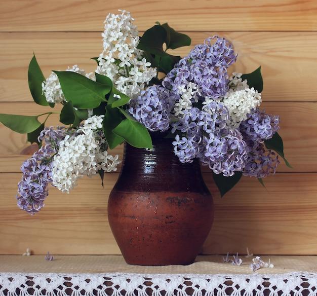 Lillà in una brocca su un fondo di legno. bouquet di rami fioriti.