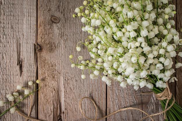 Lilly della valle in vaso di vetro sul tavolo di legno.