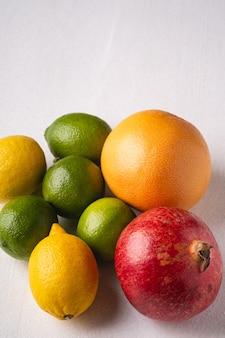 Lime, limone, pompelmo e melograno su bianco