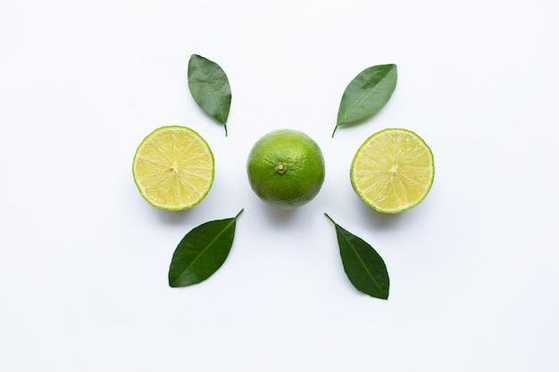 Limes maturo con foglie verdi su bianco.