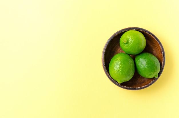Limette succose fresche su un piatto di argilla marrone su un giallo