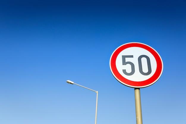 Limite di velocità del segnale stradale sul cielo senza nuvole blu e sulla lampada di via.