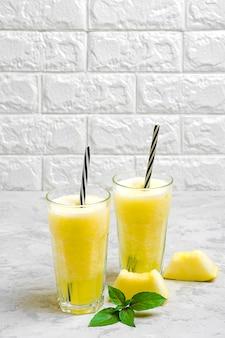 Limonata al melone, frullato con ghiaccio e basilico in un bicchiere sul tavolo grigio. bevanda rinfrescante e disintossicante estiva stile rustico