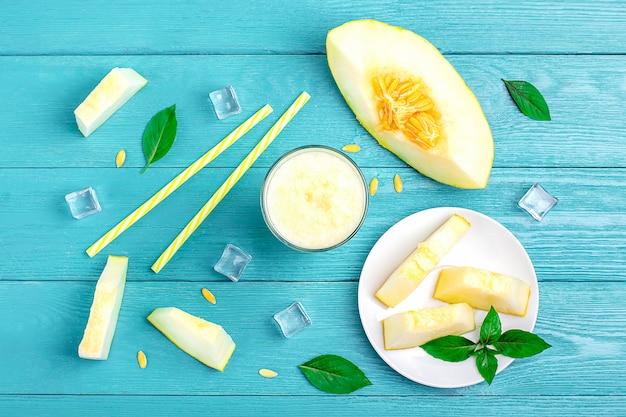 Limonata al melone, frullato con ghiaccio e basilico in un bicchiere, tubuli, pezzi di melone sul piatto sul tavolo di legno blu.