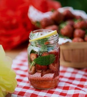 Limonata alla fragola con ghiaccio e menta come bevanda rinfrescante estiva in vasetti. bevande analcoliche fredde con frutta.