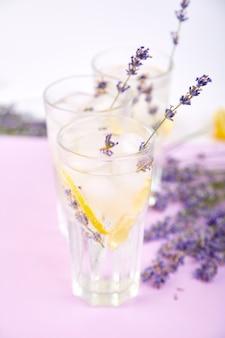 Limonata alla lavanda con limone e ghiaccio su sfondo viola.