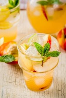 Limonata alla pesca e lime, cocktail mojito con contorno di frutta fresca