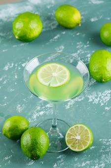 Limonata con limoni in un bicchiere su intonaco, veduta dall'alto.