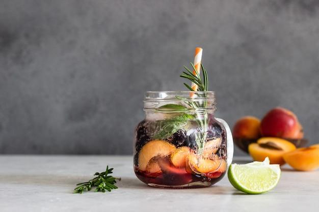 Limonata di albicocca e ribes nero in vetro con albicocca, rosmarino, menta e lime.