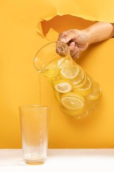 Limonata di versamento della mano del primo piano in un vetro