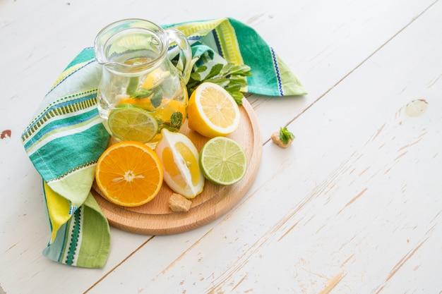 Limonata ed ingredienti su fondo di legno bianco