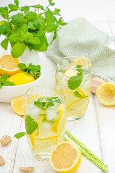 Limonata fatta in casa con fette di limone, menta e zucchero di canna in un bicchiere con ghiaccio su un tavolo di legno bianco.