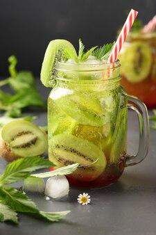 Limonata fatta in casa con kiwi, limone e menta in un bicchiere trasparente contro una superficie scura, formato verticale