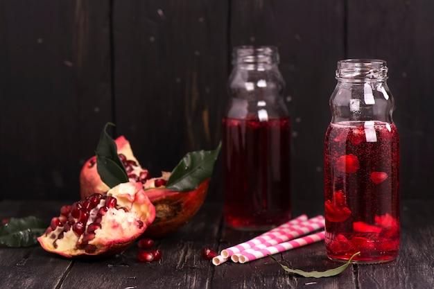 Limonata fatta in casa con melograno rosso in piccole bottiglie di vetro