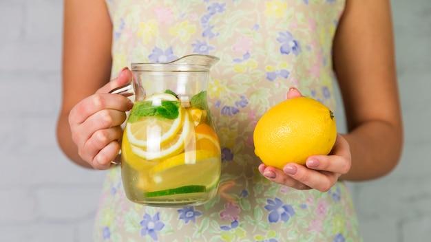 Limonata fatta in casa e limone tenuti da una donna