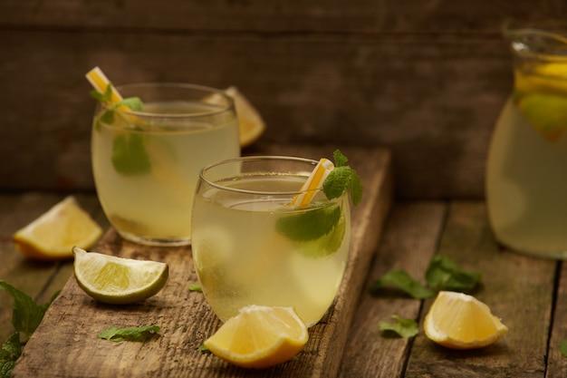 Limonata fatta in casa in due bicchieri con cannucce sul vecchio tavolo di legno