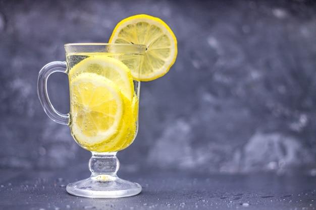 Limonata fatta in casa in un bicchiere con una maniglia su uno sfondo grigio cemento. acqua con fette di limone