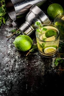 Limonata fatta in casa o mojito cocktail con foglie di menta e lime fresche, metallo arrugginito scuro,