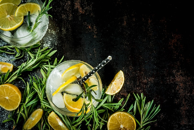Limonata fredda o alcol vodka cocktail con limone e rosmarino, su un nero arrugginito metallico,
