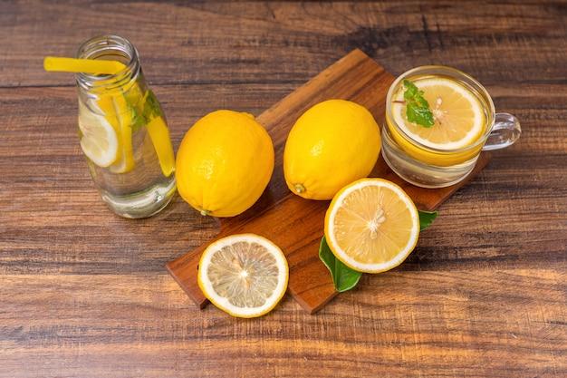 Limonata fresca che beve con l'erba nel cocktail di vetro, della calce o di mojito con il limone sulla tavola di legno per lo spazio della copia di estate calda