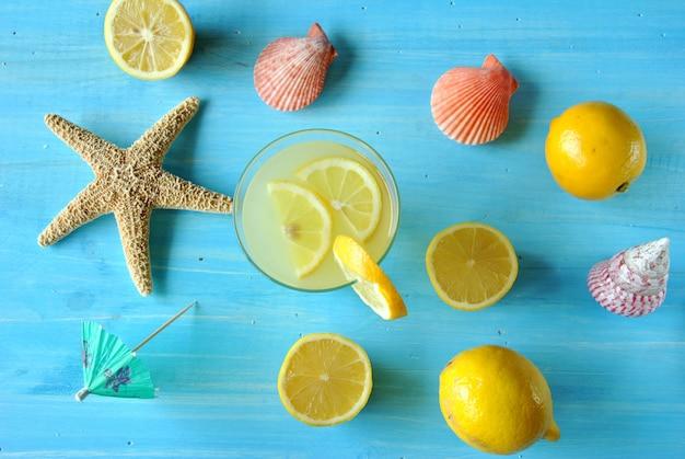 Limonata fresca con stelle marine e conchiglie sul tavolo blu