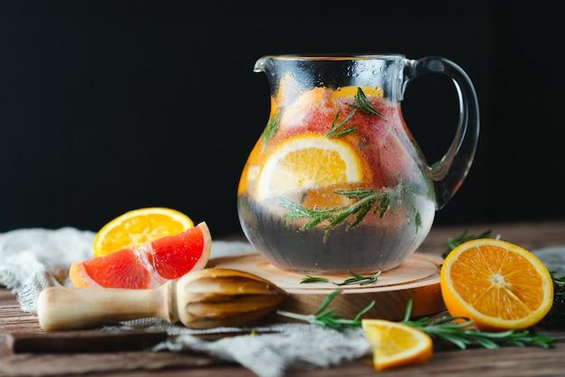 Limonata fresca estiva con pompelmo e rosmarino su un vecchio tavolo di legno. concetto di estate.