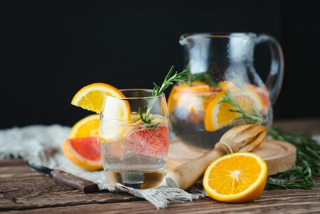 Limonata fresca estiva con pompelmo e rosmarino su un vecchio tavolo di legno