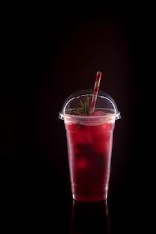 Limonata fresca rinfrescante con fragole, menta e ghiaccio in un bicchiere di plastica con coperchio su sfondo nero