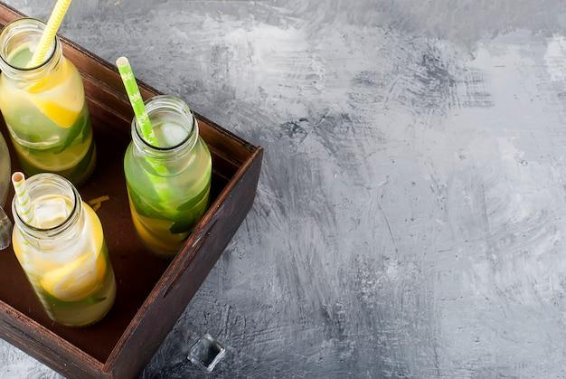 Limonata in bottiglia con ghiaccio e menta