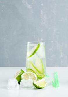 Limonata in un bicchiere con limone, cannucce, cubetti di ghiaccio vista laterale su bianco e gesso