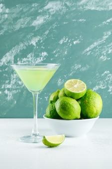 Limonata in un bicchiere con vista laterale di limoni su bianco e gesso